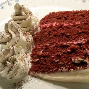 Slice of red velvet cake with whipped cream and cocoa